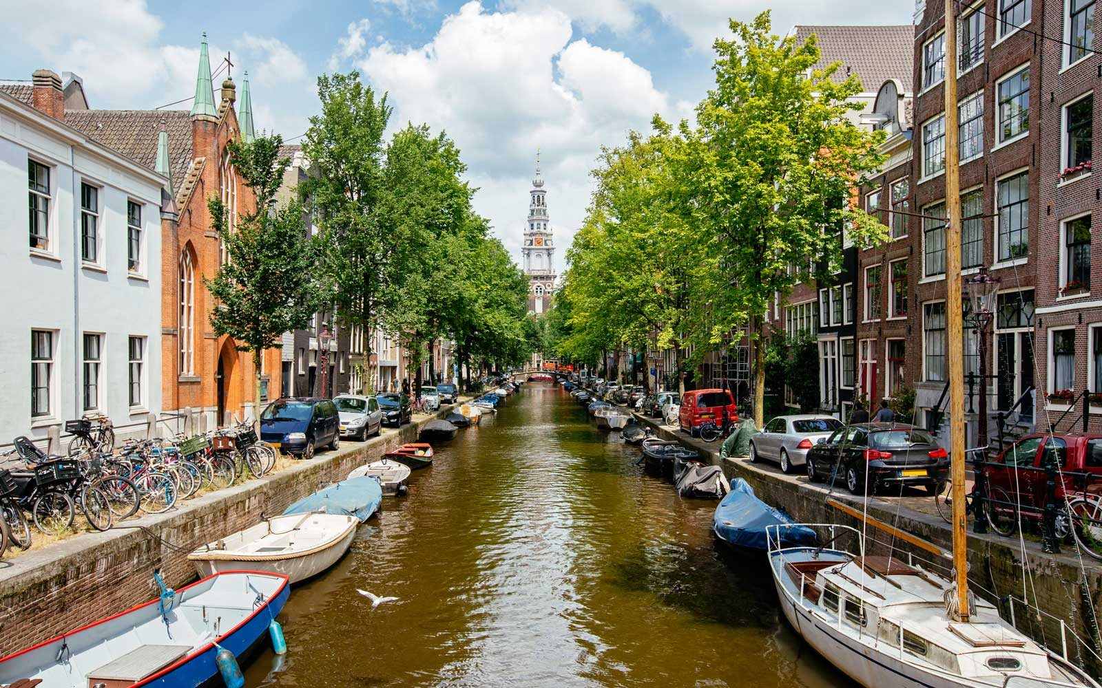 Church and boats moored along the canal in Amsterdam, Holland