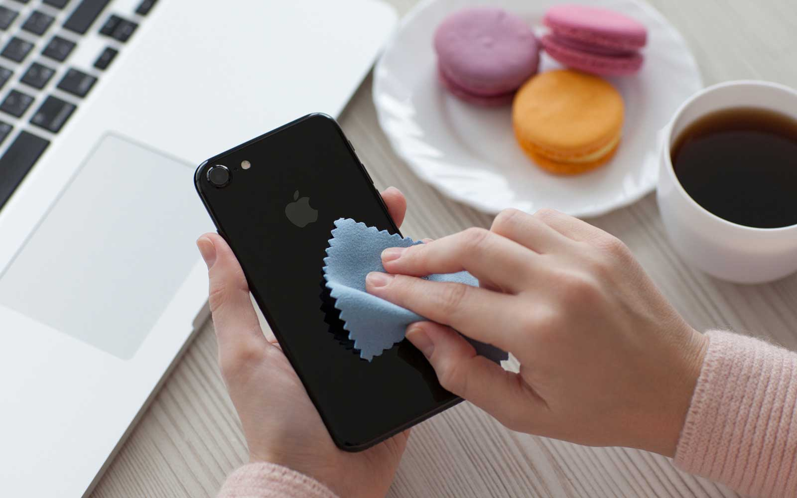 Woman holding iPhone 7 Jet Black Onyx and cleaning it