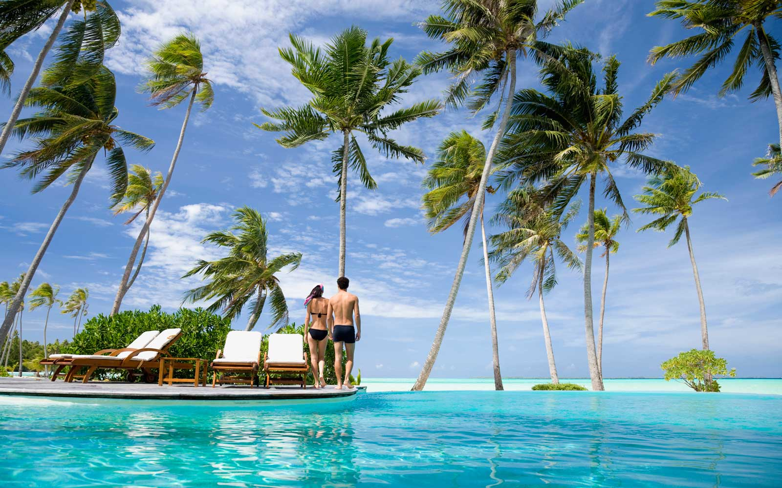 Couple walking past a resort pool, with palm trees