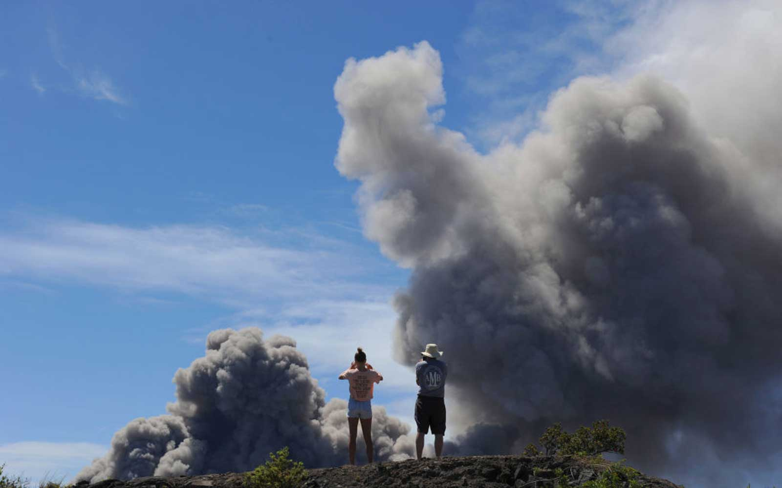 Tourists and locals alike view the plumes of smoke coming from the Halemaumau Vent of the Kilauea Volcano