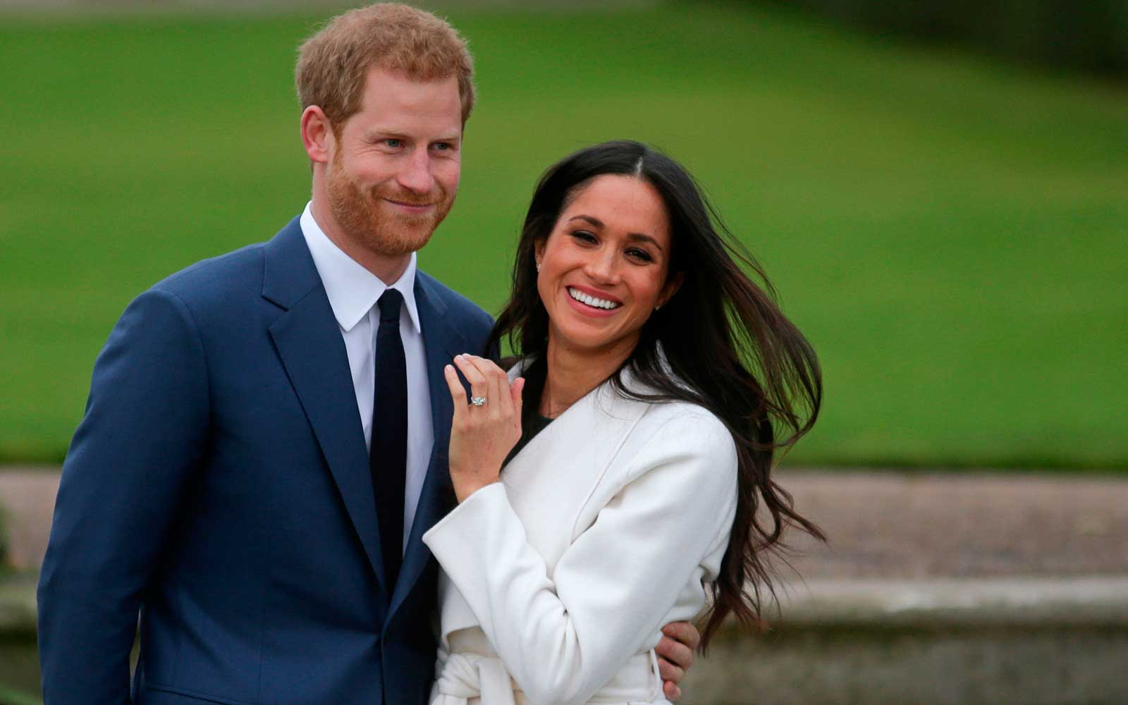 Britain's Prince Harry stands with his fiancée US actress Meghan Markle as she shows off her engagement ring whilst they pose for a photograph in the Sunken Garden at Kensington Palace