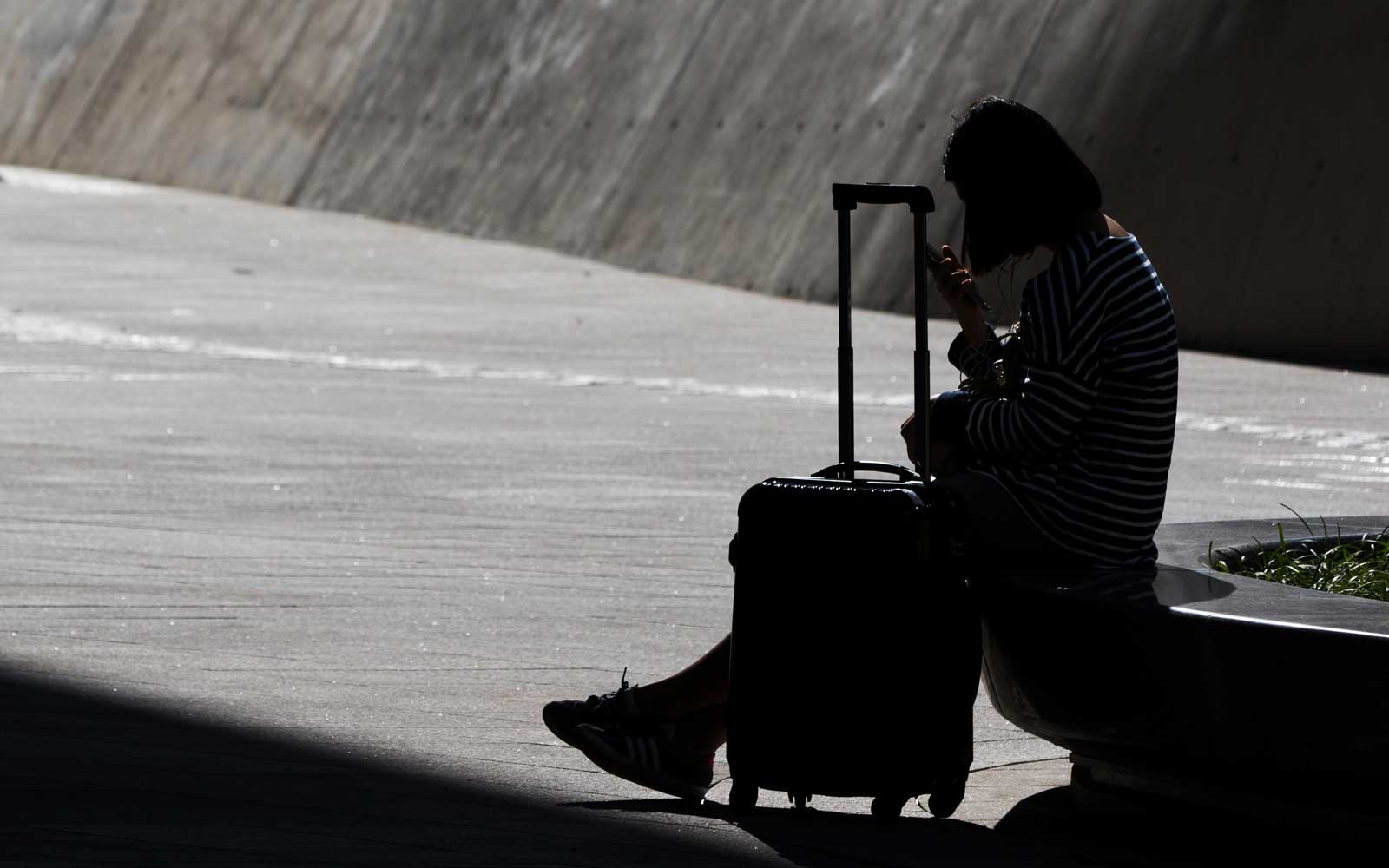 A woman sitting near luggage uses her smartphone