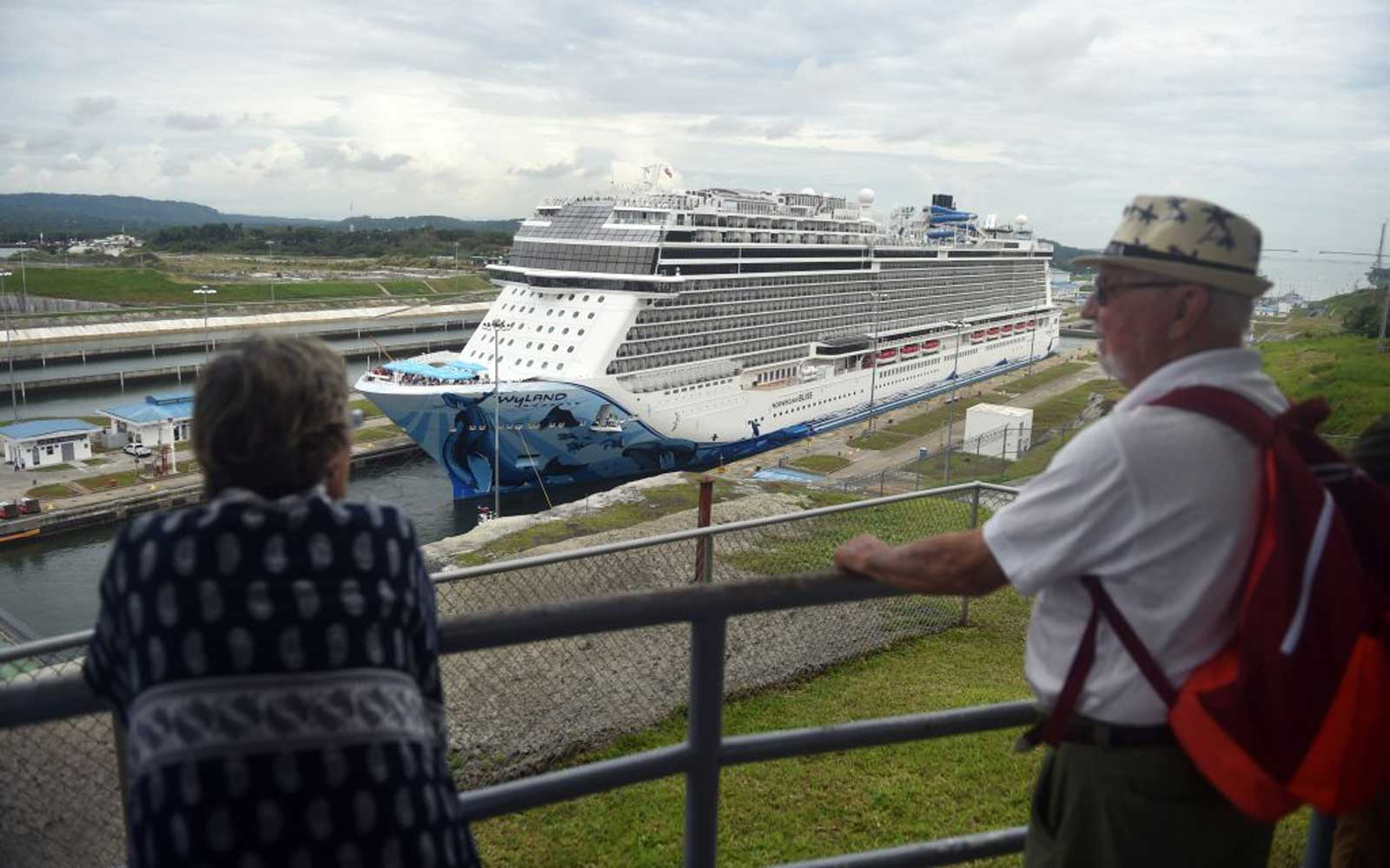 Tourists look at a cruise ship crossing the Panama Canal in the Agua Clara locks in Colon 80 km northwest from Panama City