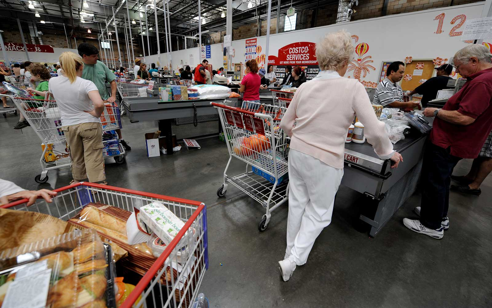 People shop at the reduced cost, high volume Costco supermarket warehouse