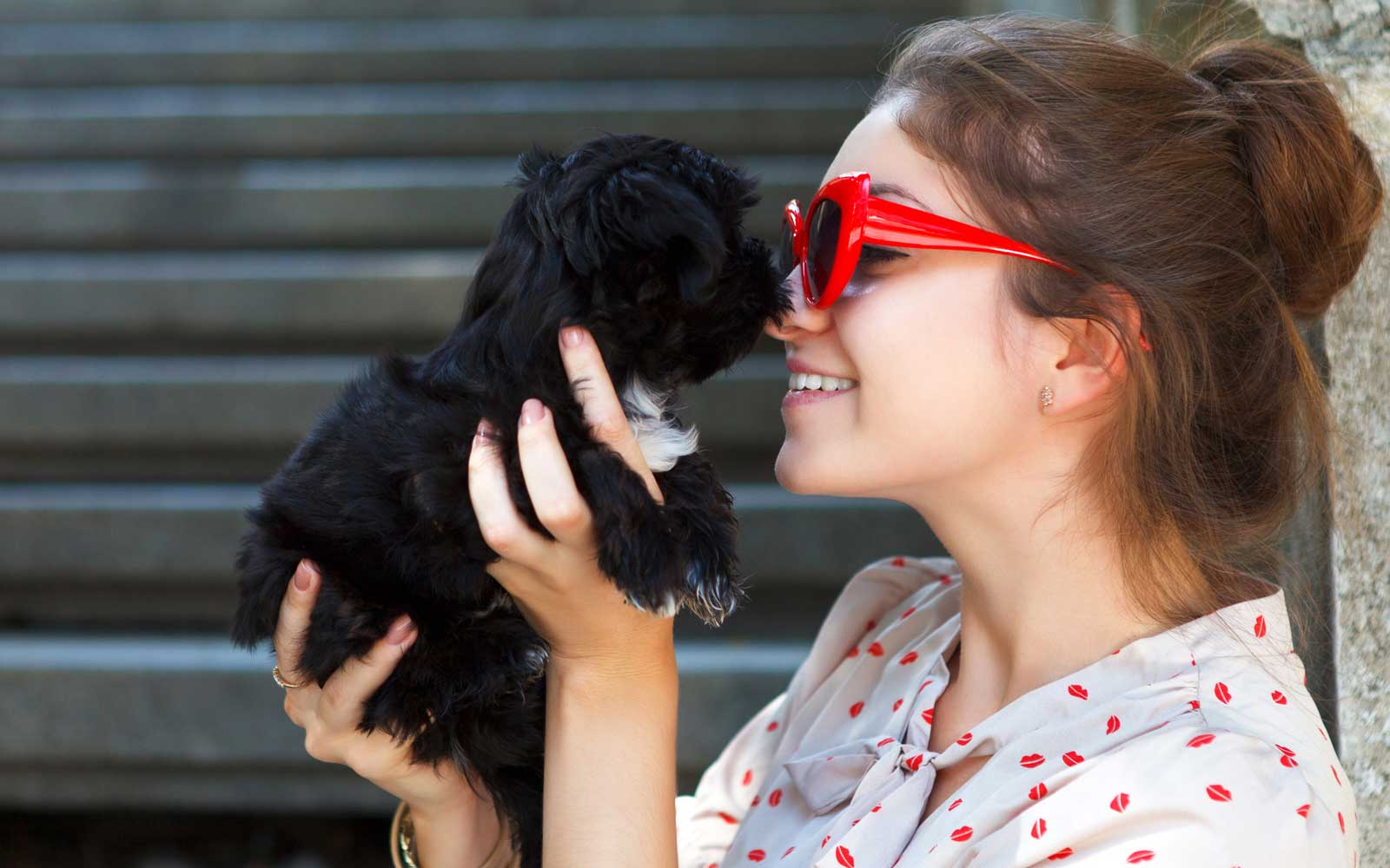 Young brunette woman hugging her lap dog puppy