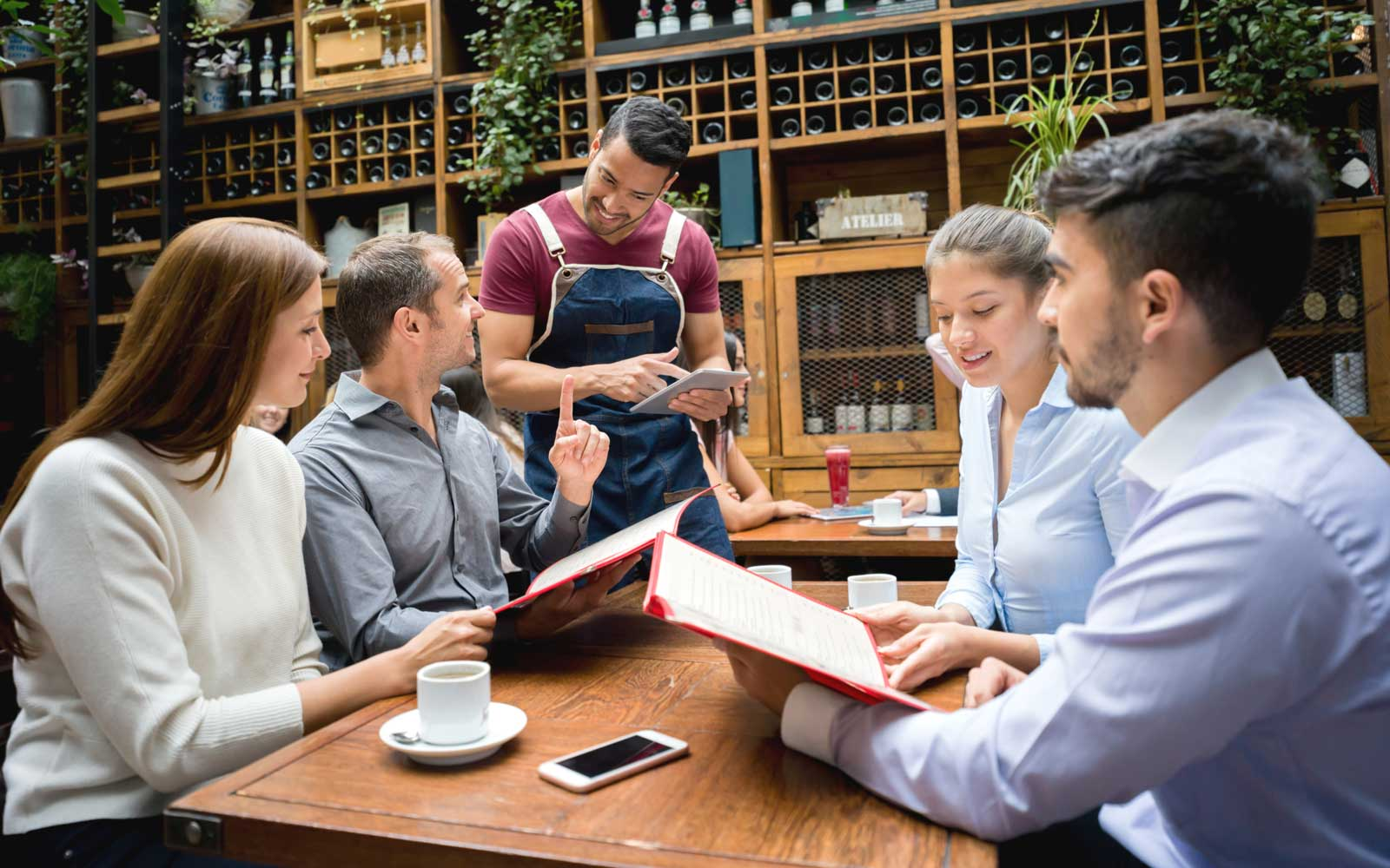 Waiter taking order to a group at a restaurant using a tablet