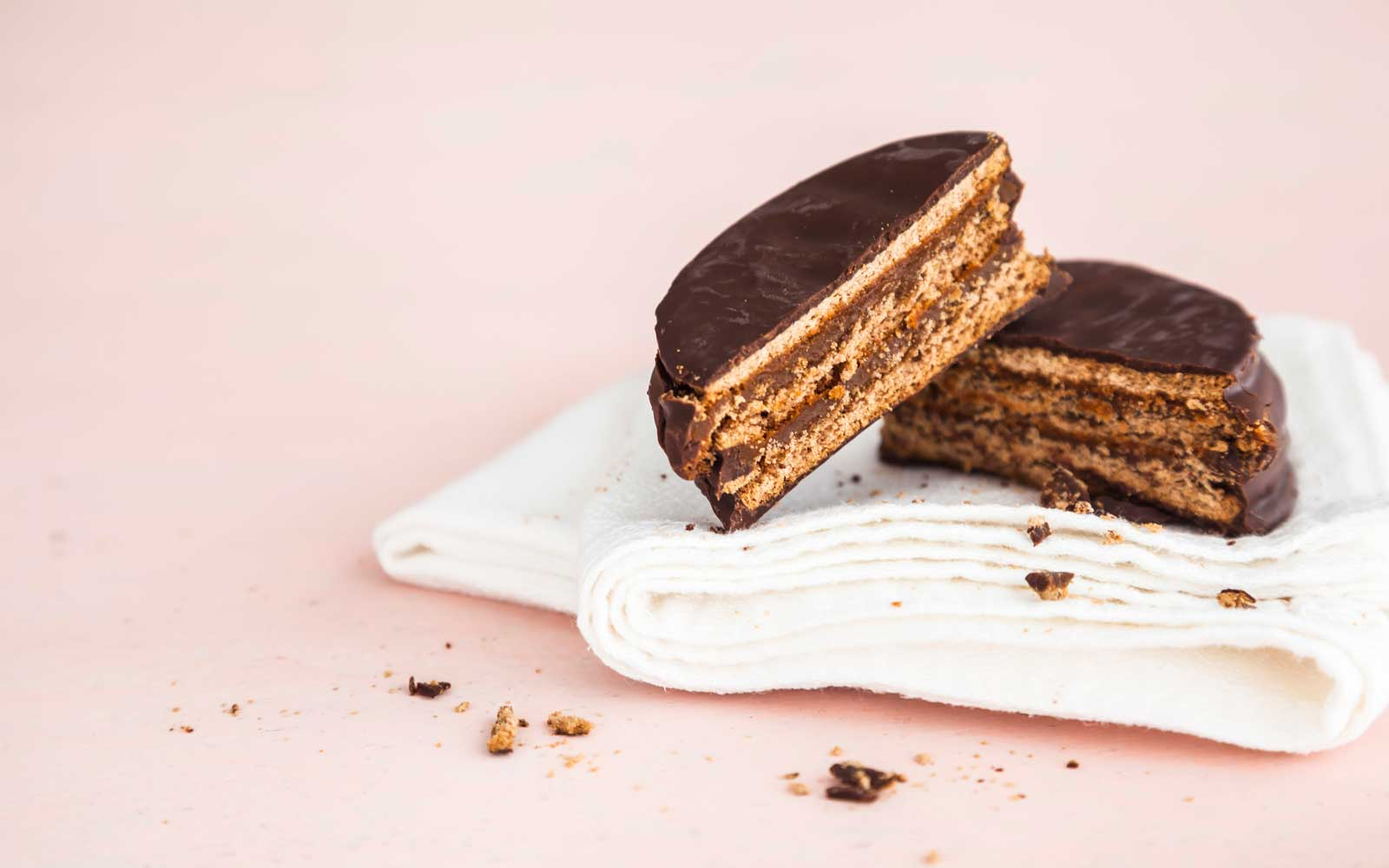 Alfajor, a traditional Argentine pastry made with chocolate and 'dulce de leche', over napkin against pink background