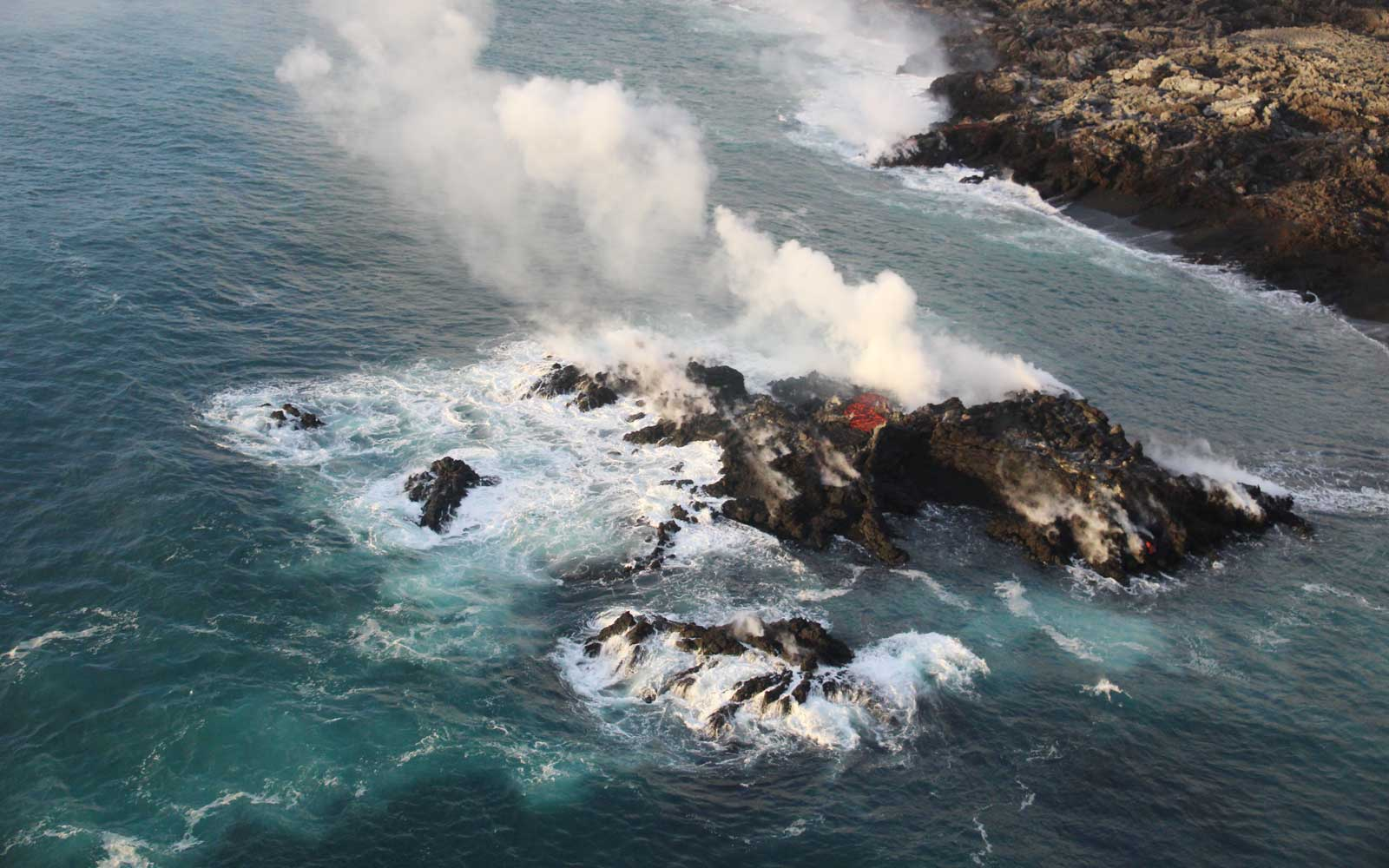 Tight shot of new island off the coast of Hawaii, formed by lava flowing into the ocean