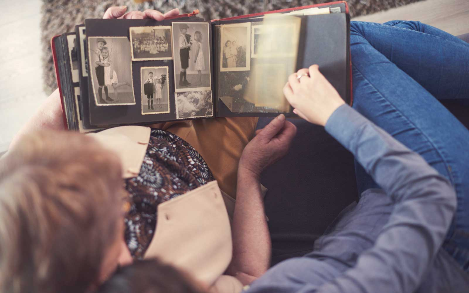 Overhead view of young woman on sofa with grandmother looking at photo album
