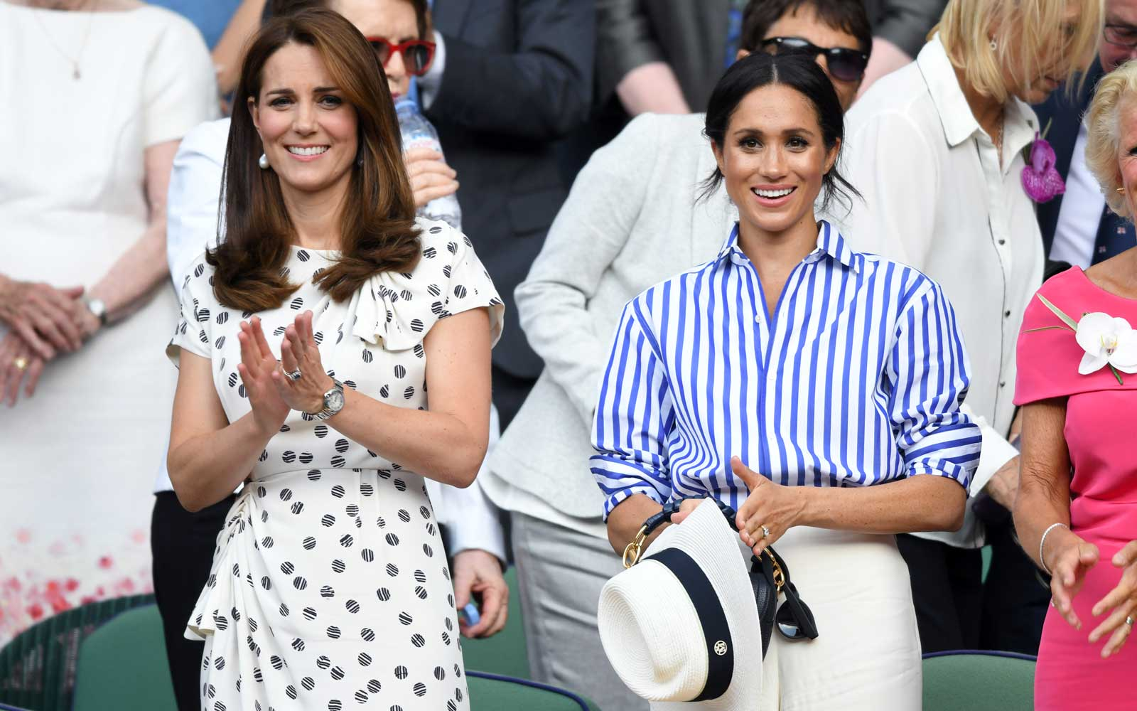 Meghan Markle holding her hat at Wimbledon
