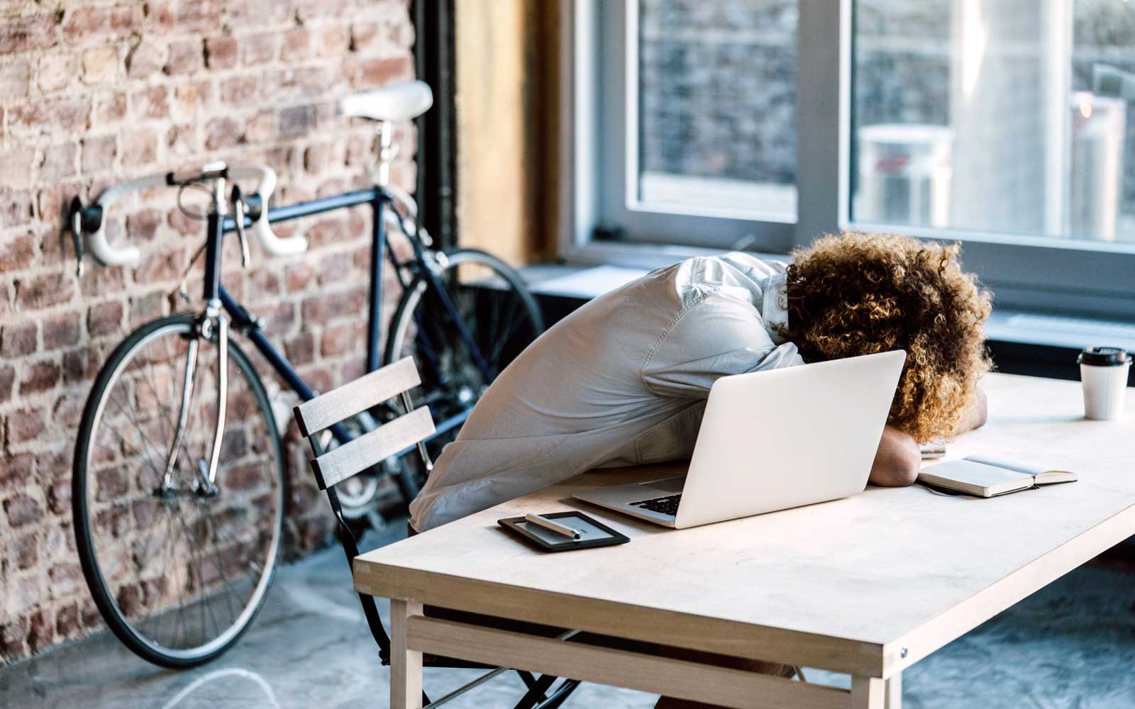 Person laying on desk, exhausted and working