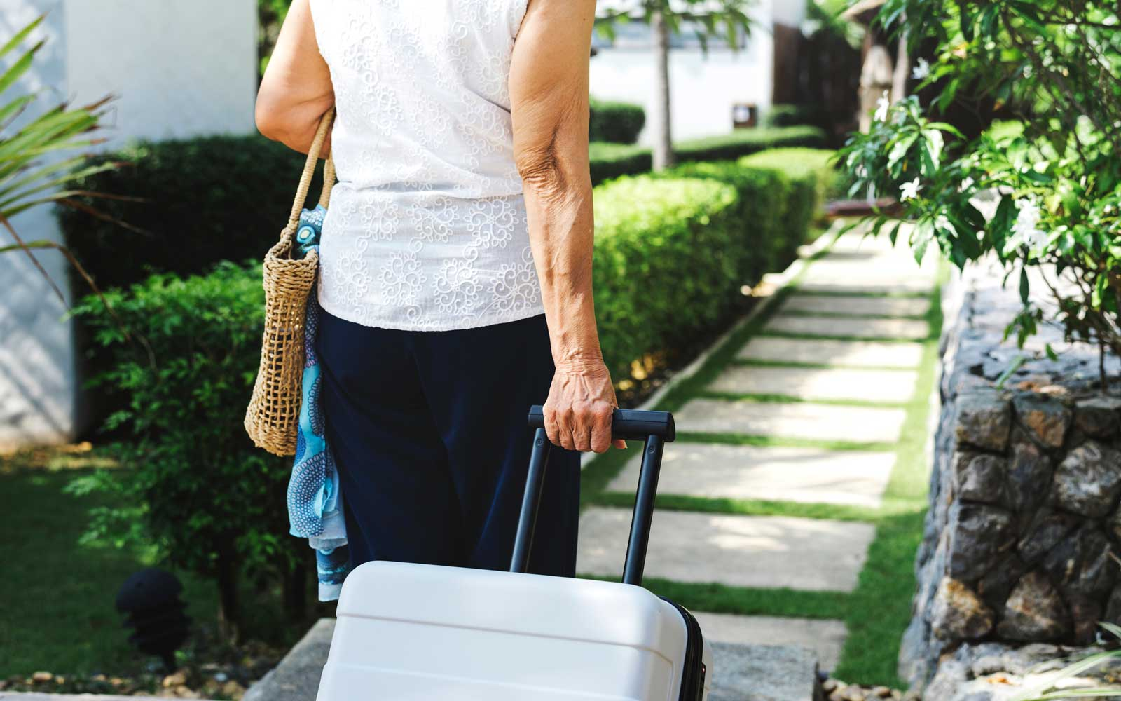 Senior woman pulling suitcase and walking