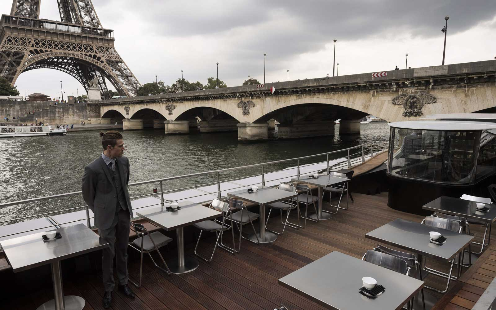 "A waiter stands at French chef Alain Ducasse's new boat restaurant, the ""Ducasse sur Seine"", on August 30, 2018 in Paris, next to the Eiffel tower"