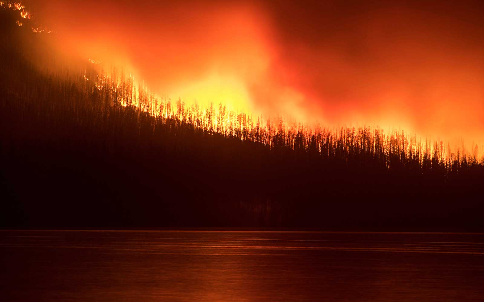 Sunday, Aug. 12, 2018, a fire burns next to Lake McDonald in Glacier National Park in northwest Montana.