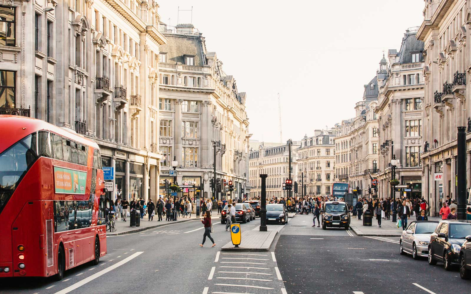 Busy day on Regent street with crowds of people and cars, London, England, UK