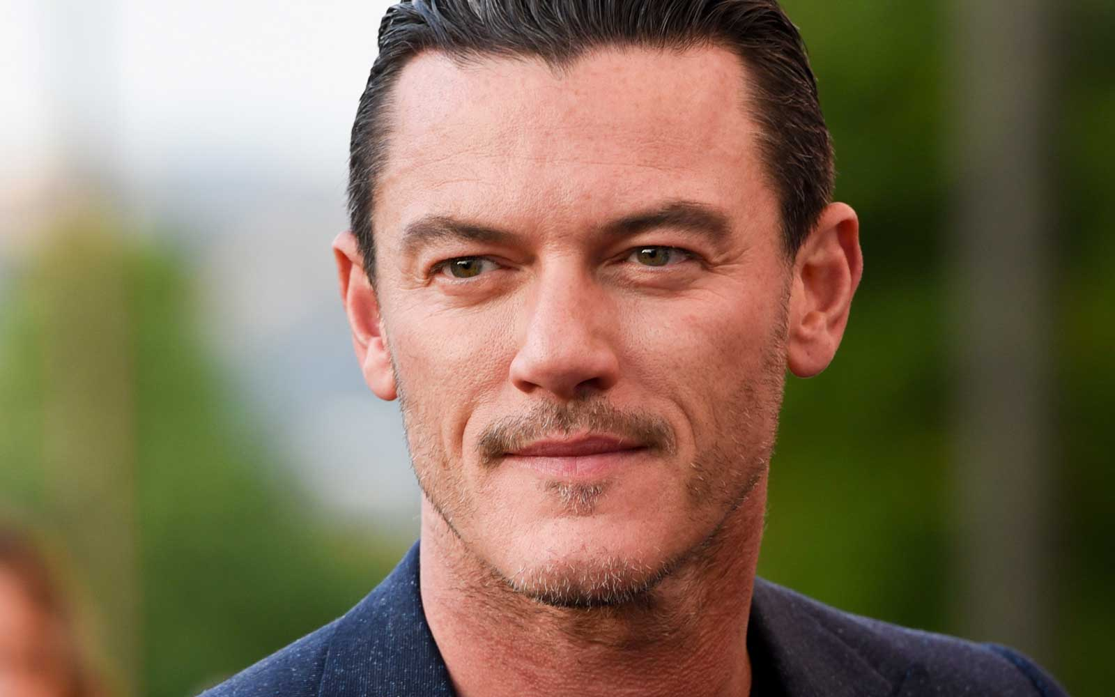 Luke Evans Reveals What It's Like Traveling Italy With Jennifer Aniston and Adam Sandler