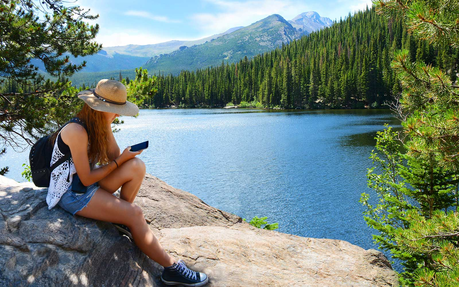 Woman using a cell phone by a lake while on vacation