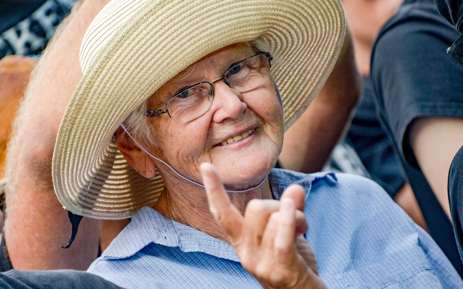Germany, Wacken: An older visitor of the Wacken Open Air celebrates the performance of the local fire brigade band with the metal greeting, the  devil horns  hand gesture.