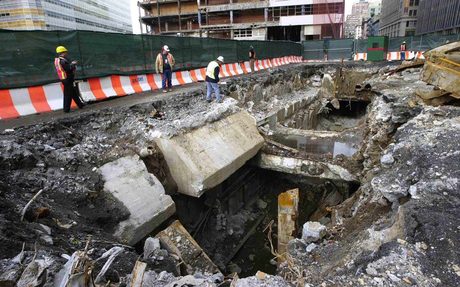 Workers look into the gaping hole near the Cortlandt St. station after the No. 1 and 9 subway lines collapsed under the demolished World Trade Center.