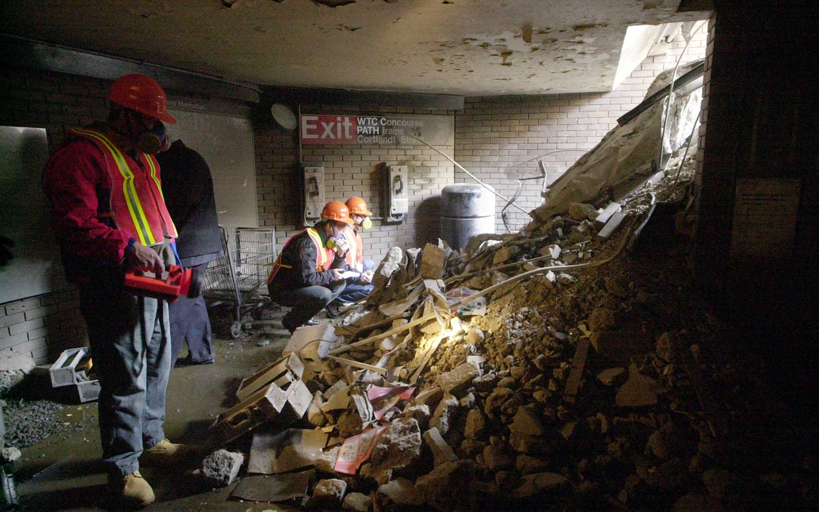 Workers look over the mass of rubble that used to be the staircase leading down to the Cortlandt St. station which was destroyed after the No. 1 and 9 subway lines collapsed under the demolished World Trade Center.