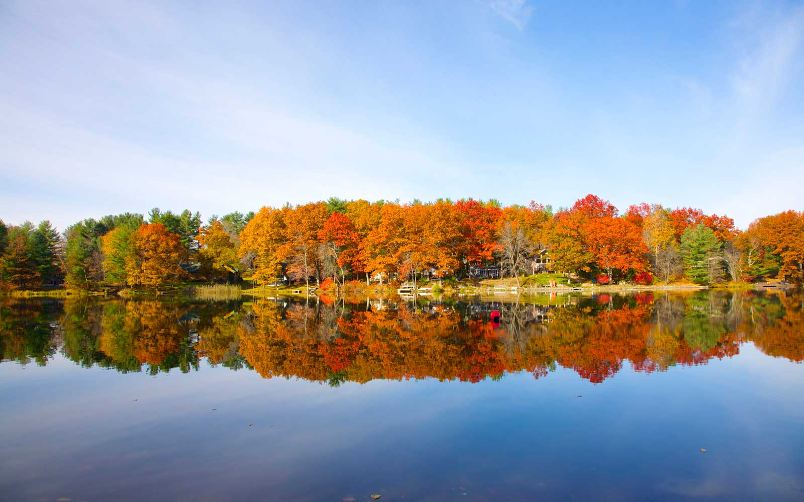 Lakeside trees with leaves changing to oranges and reds in early fall, Columbia County, New York State, USA.