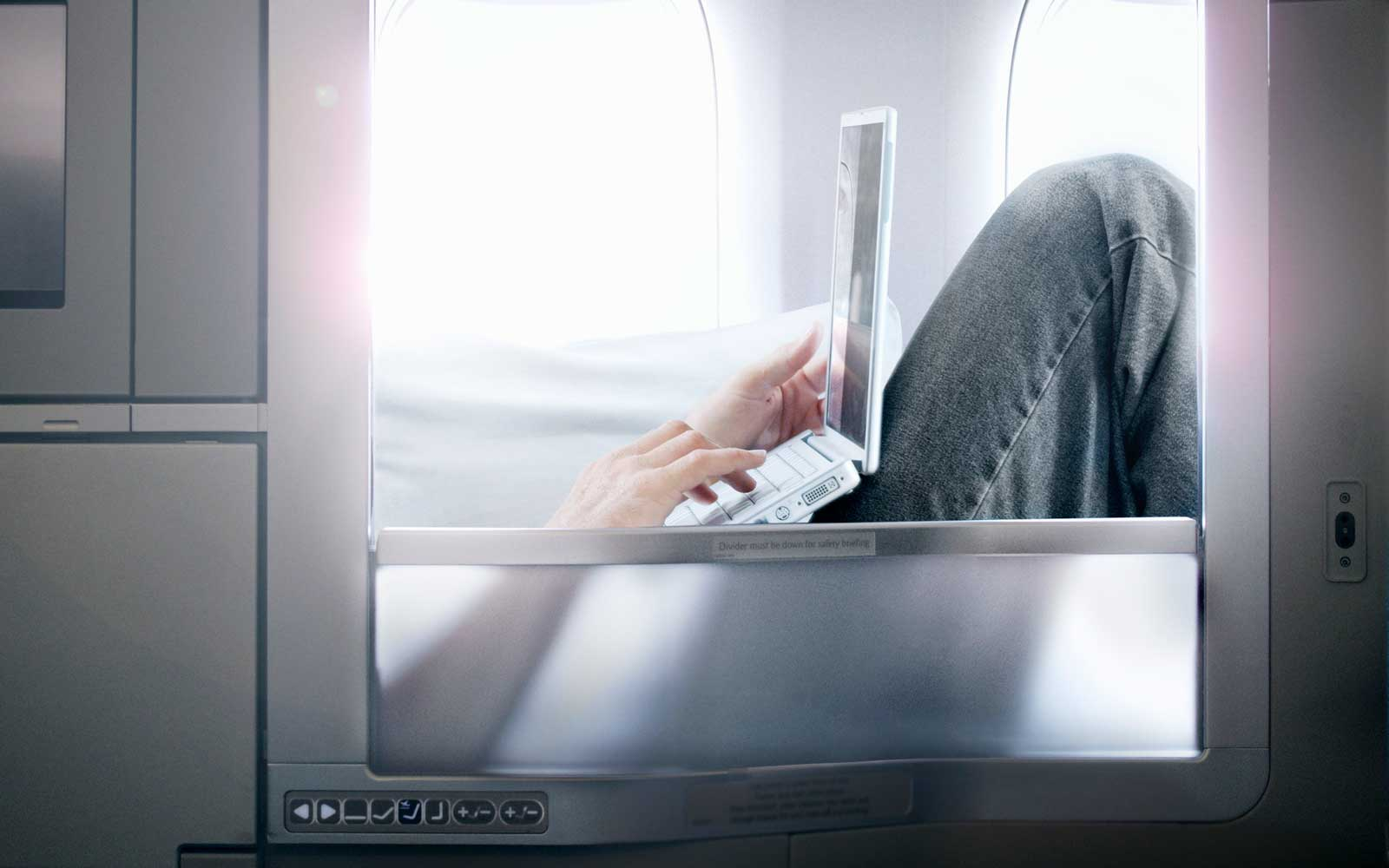 Man on airplane in first class with laptop