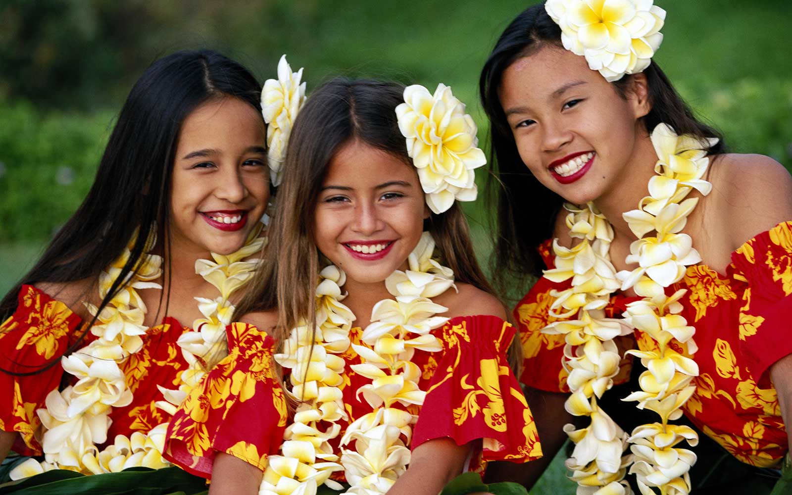 Three girls in colorful hula outfits, matching w/ plumeria lei & flowers, smiling Hawaii Maui