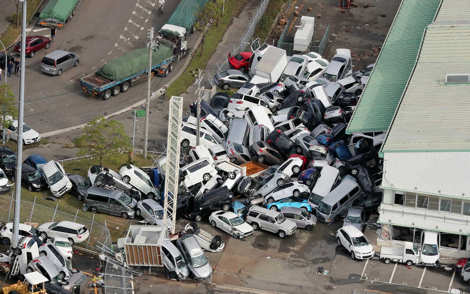 An aerial view from a Jiji Press helicopter shows vehicles piled in a heap due to strong winds in Kobe, Hyogo prefecture on September 5, 2018, after typhoon Jebi hit the west coast of Japan.