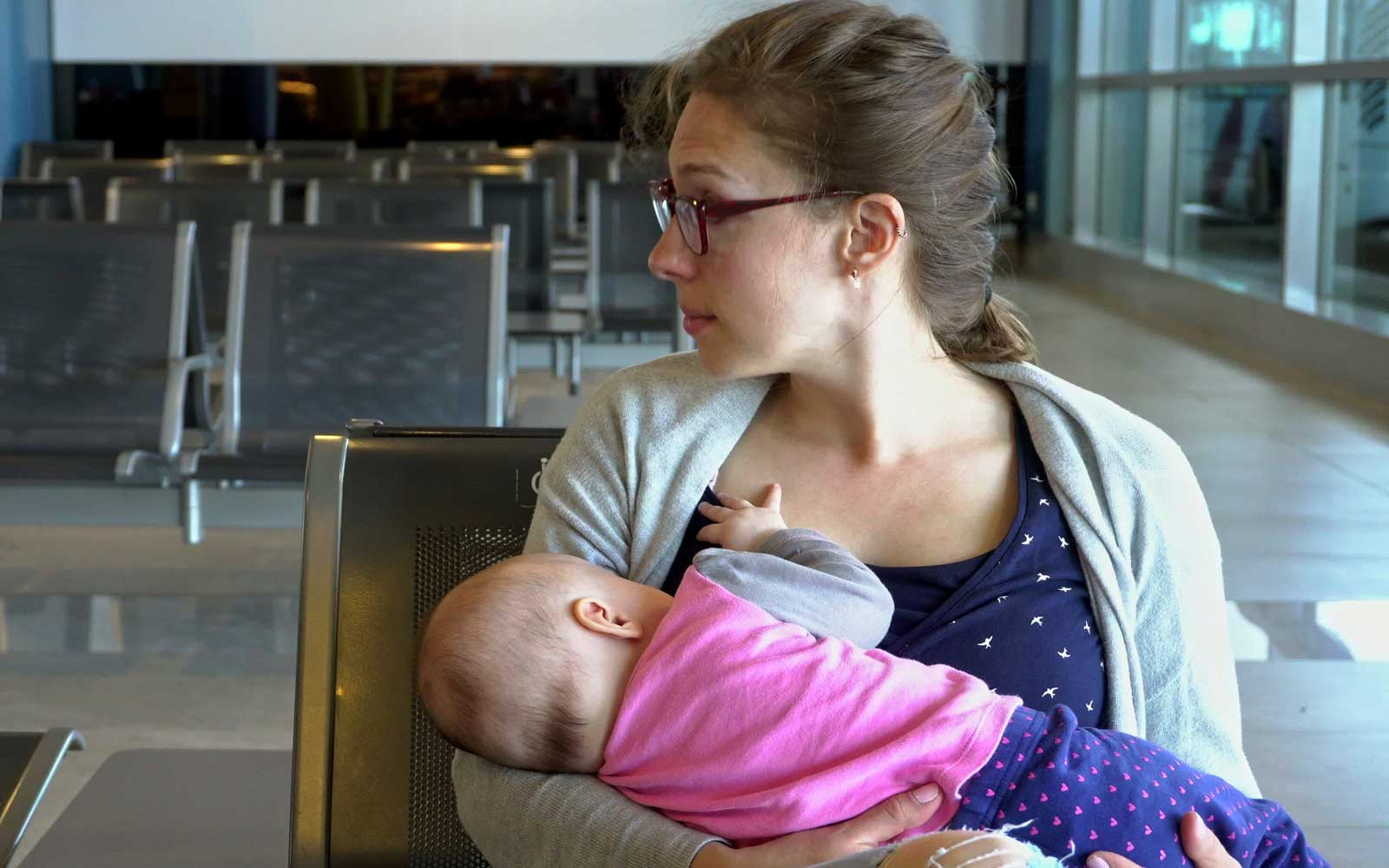 A Woman Breastfeeding her Child at the Airport