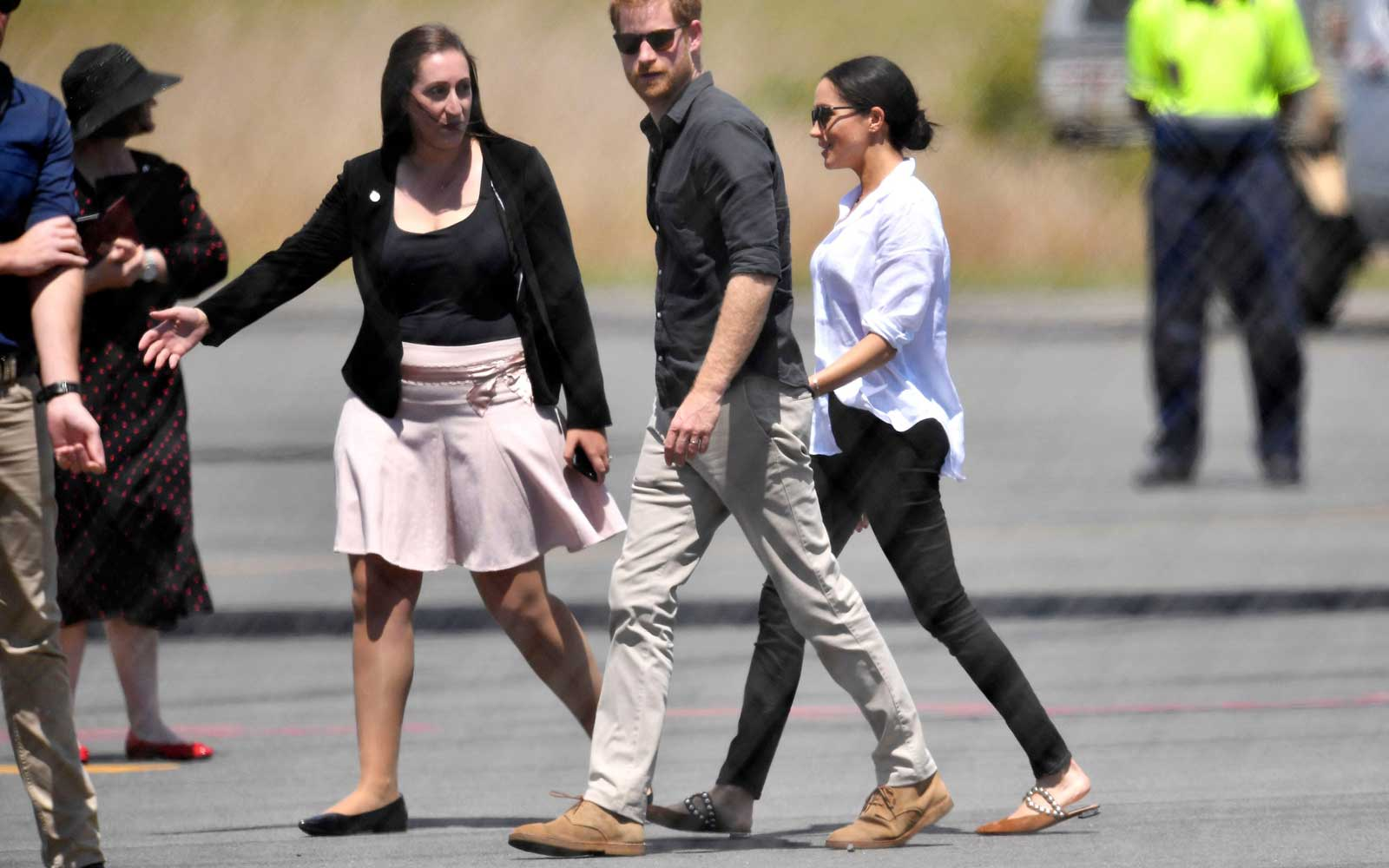 Britain's Prince Harry (C), the Duke of Sussex, and his wife Meghan (R), the Duchess of Sussex, prepare to board a plane at Hervey Bay Airport in Hervey Bay, Australia, 23 October 2018.
