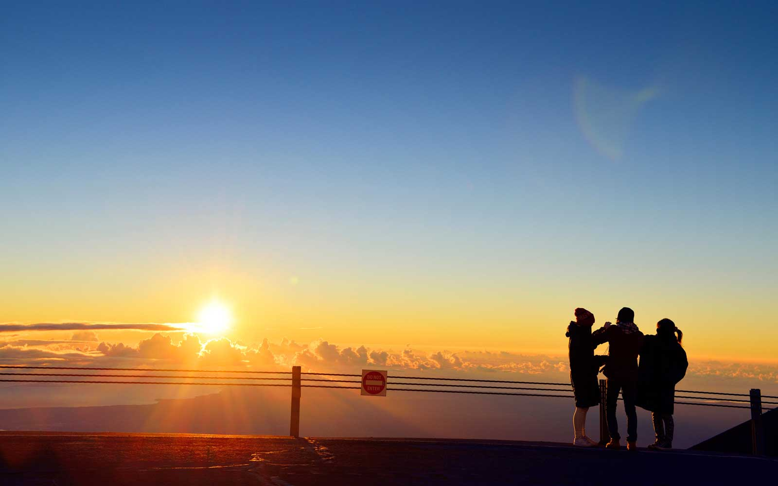 USA, Hawaii, Big Island, Mauna Kea, three tourists watching sunrise