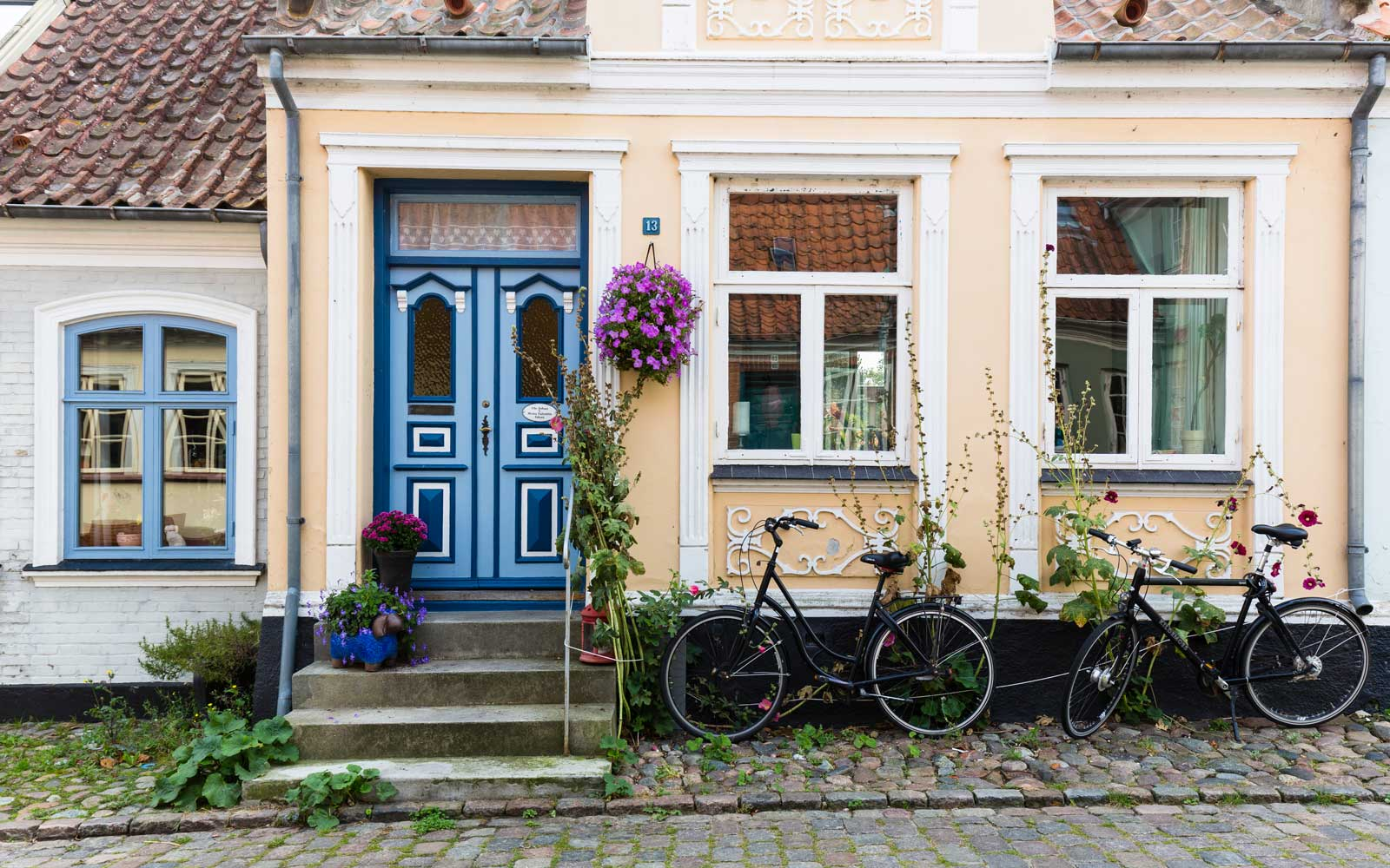 Two bicybles in front of a house with a blue door in a cobblestone alley of Aeroskobing, Aero Island