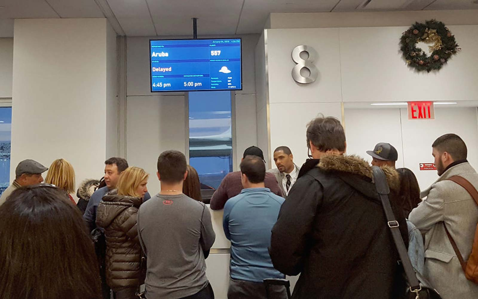 Passengers wait for their delayed flights at gate 8 in terminal five at John F. Kennedy International Airport