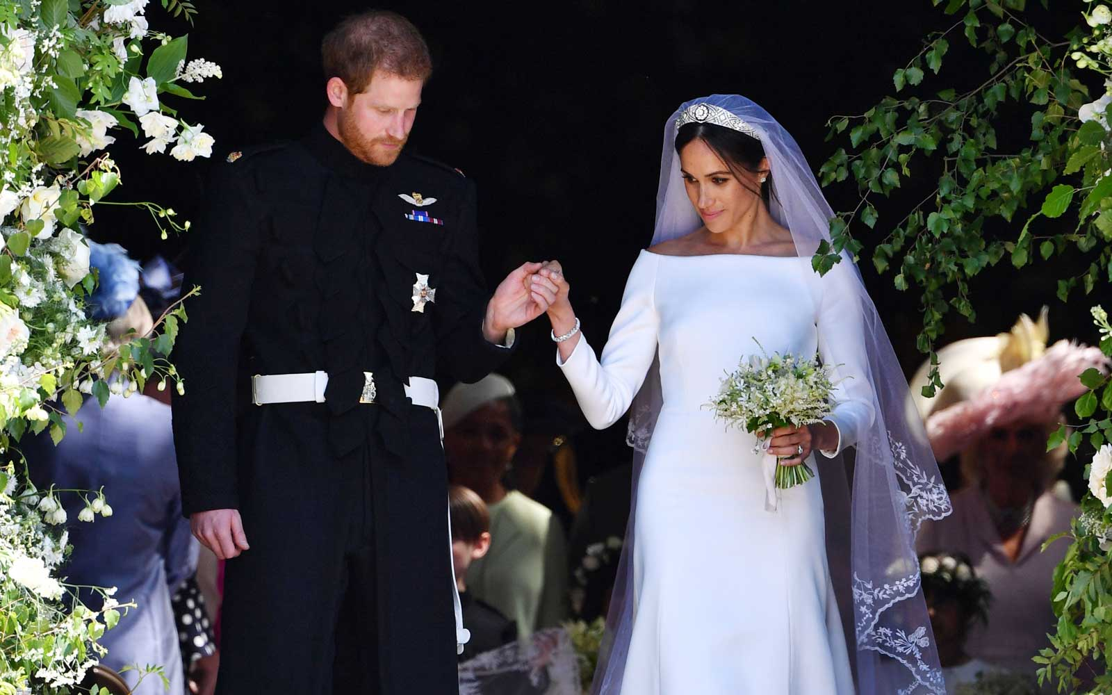 Britain's Prince Harry, Duke of Sussex and his wife Meghan, Duchess of Sussex emerge from the West Door of St George's Chapel, Windsor Castle, in Windsor, on May 19, 2018