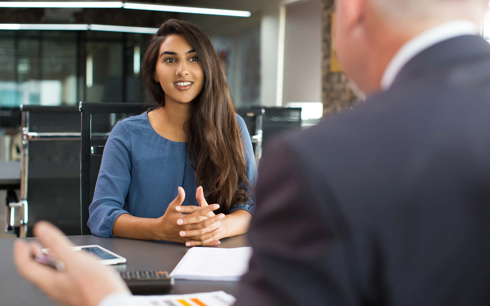 Portrait of young Indian female client or candidate sitting at table, talking to senior male manager and smiling in office