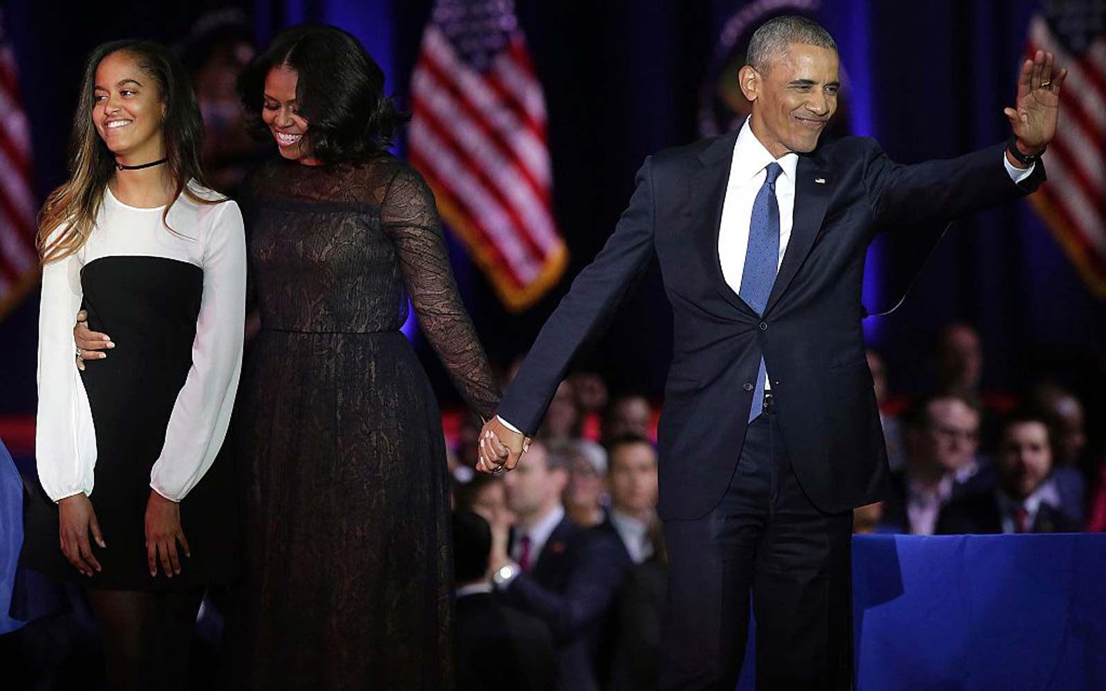 US First Lady Michelle Obama and US President Barack Obama greet supporters as daughter Malia looks on after the President delivered his farewell address in Chicago, Illinois