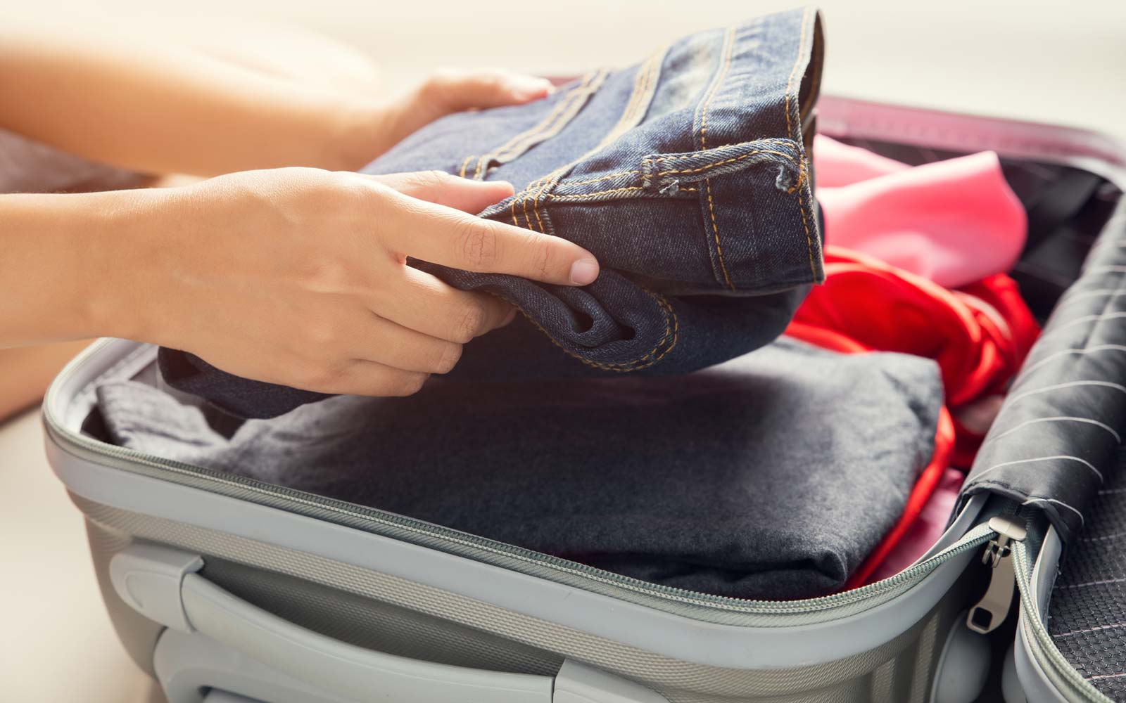 Close up of businesswoman packing clothes into travel bag - Luggage and people concept