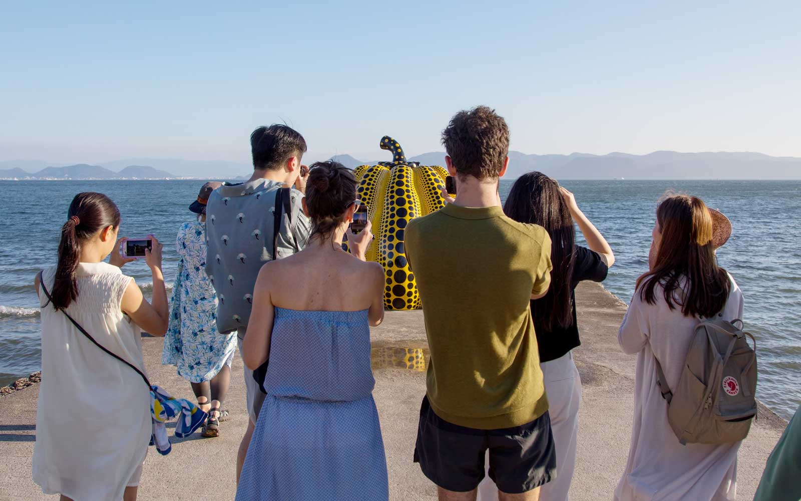 Tourists taking pictures of the yellow pumpkin by Yayoi Kusama on pier at sea, Seto Inland Sea, Naoshima, Japan
