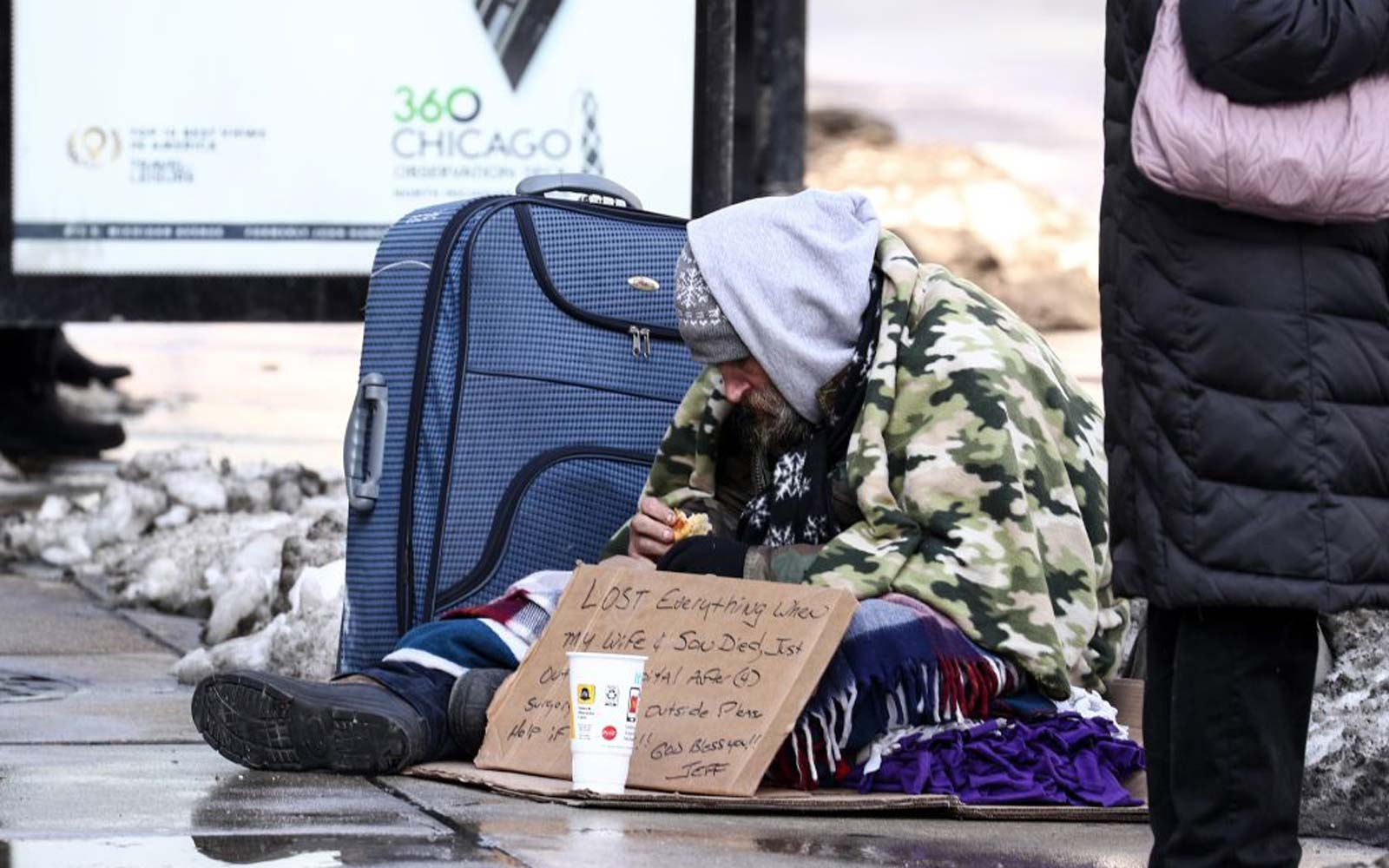 A homeless person tries to stay warm on a street while panhandling during freezing temperatures in Chicago