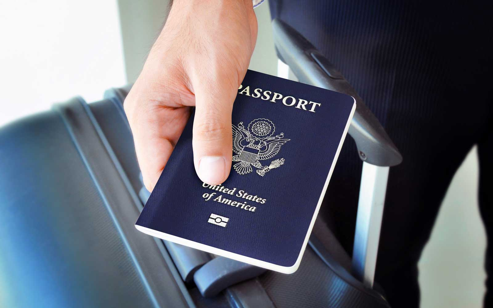 Hand holding U.S. passport in front of suitcase