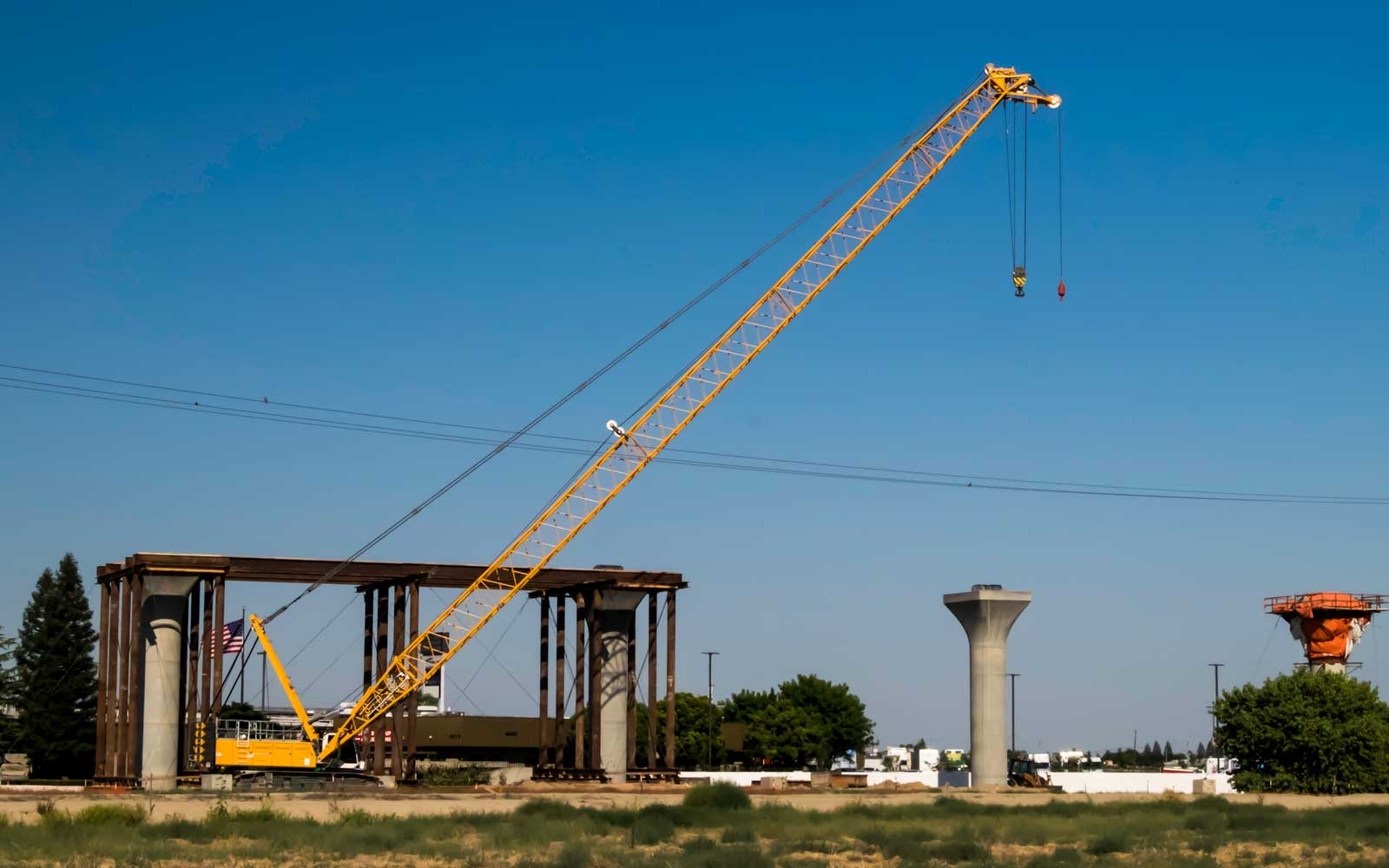 Series of cranes sitting near the high speed rail section near Nort and 99.  Fresno, CA.