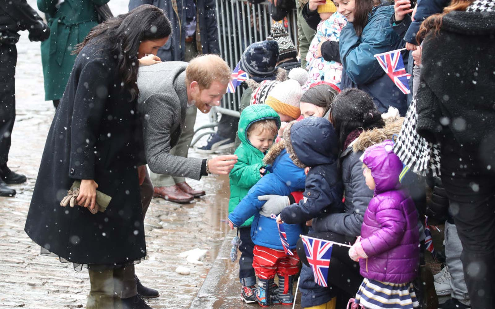 Meghan, Duchess of Sussex and Prince Harry, Duke of Sussex meet children in the crowd as they arrive at the Bristol Old Vic