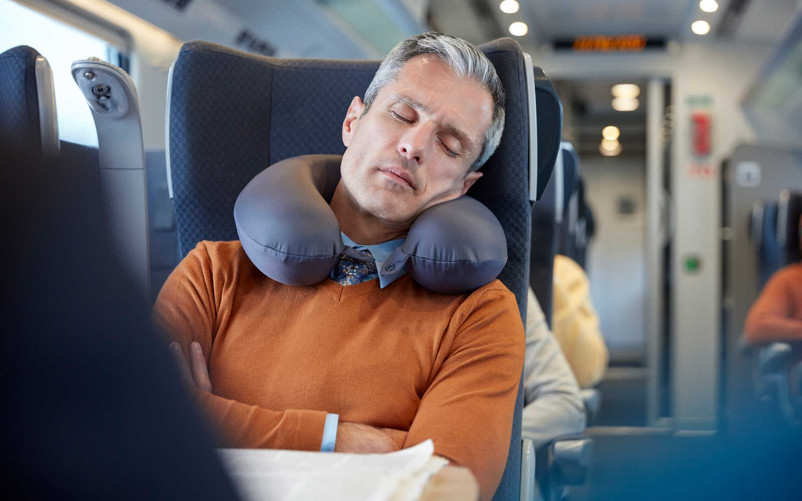man sleeping on the train with travel pillow