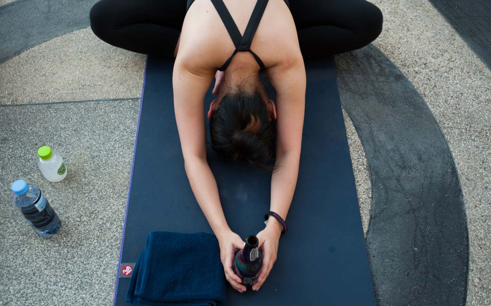 Participants in a beer yoga course perform a yoga exercise with a beer bottle