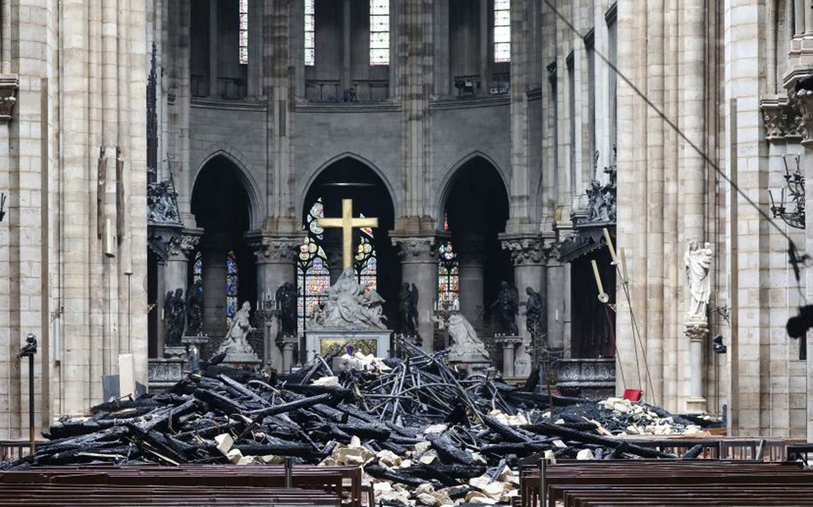 A picture taken on April 16, 2019 shows the altar surrounded by charred debris inside the Notre-Dame Cathedral in Paris in the aftermath of a fire that devastated the cathedral.