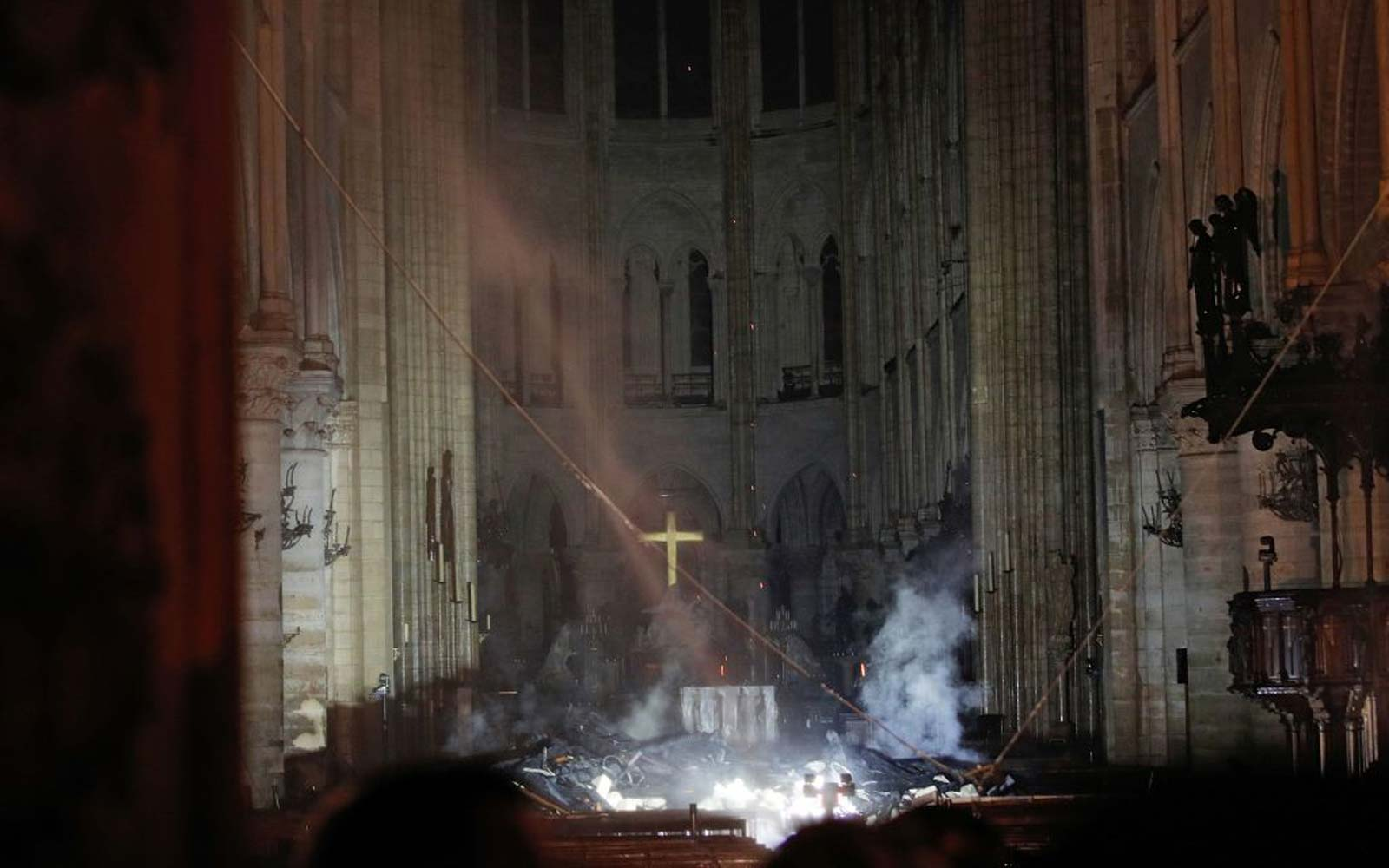 Smoke rises in front of the altar cross at Notre-Dame Cathedral in Paris