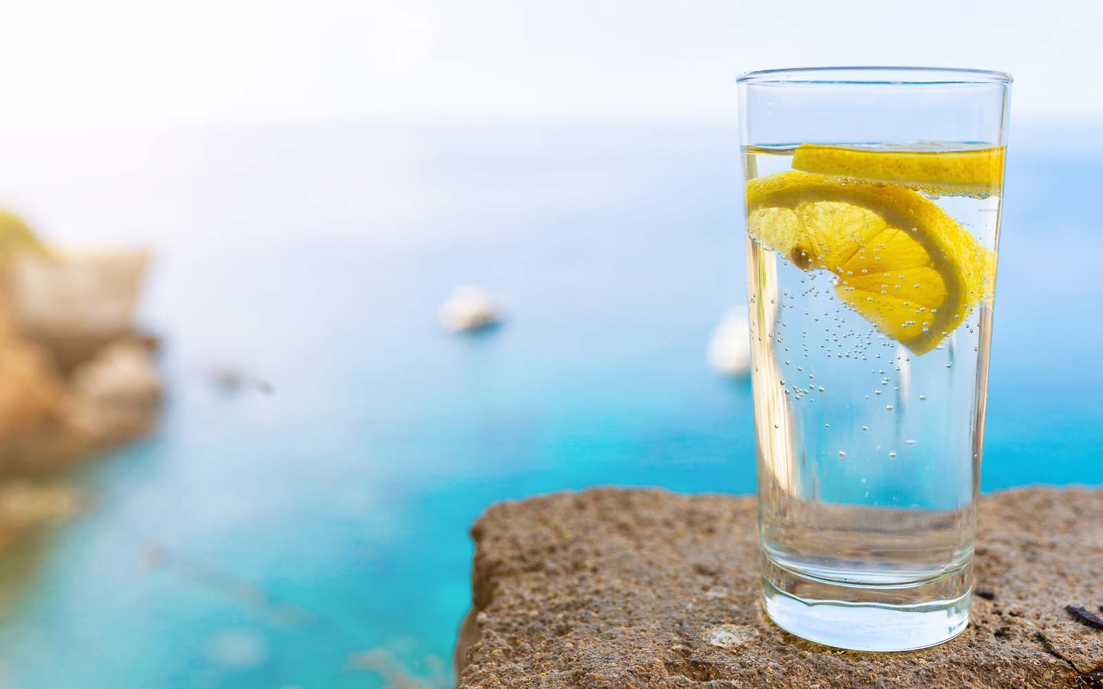 drinking glass with cold carbonated water or soft drink and lemon slice against blue sea and sky