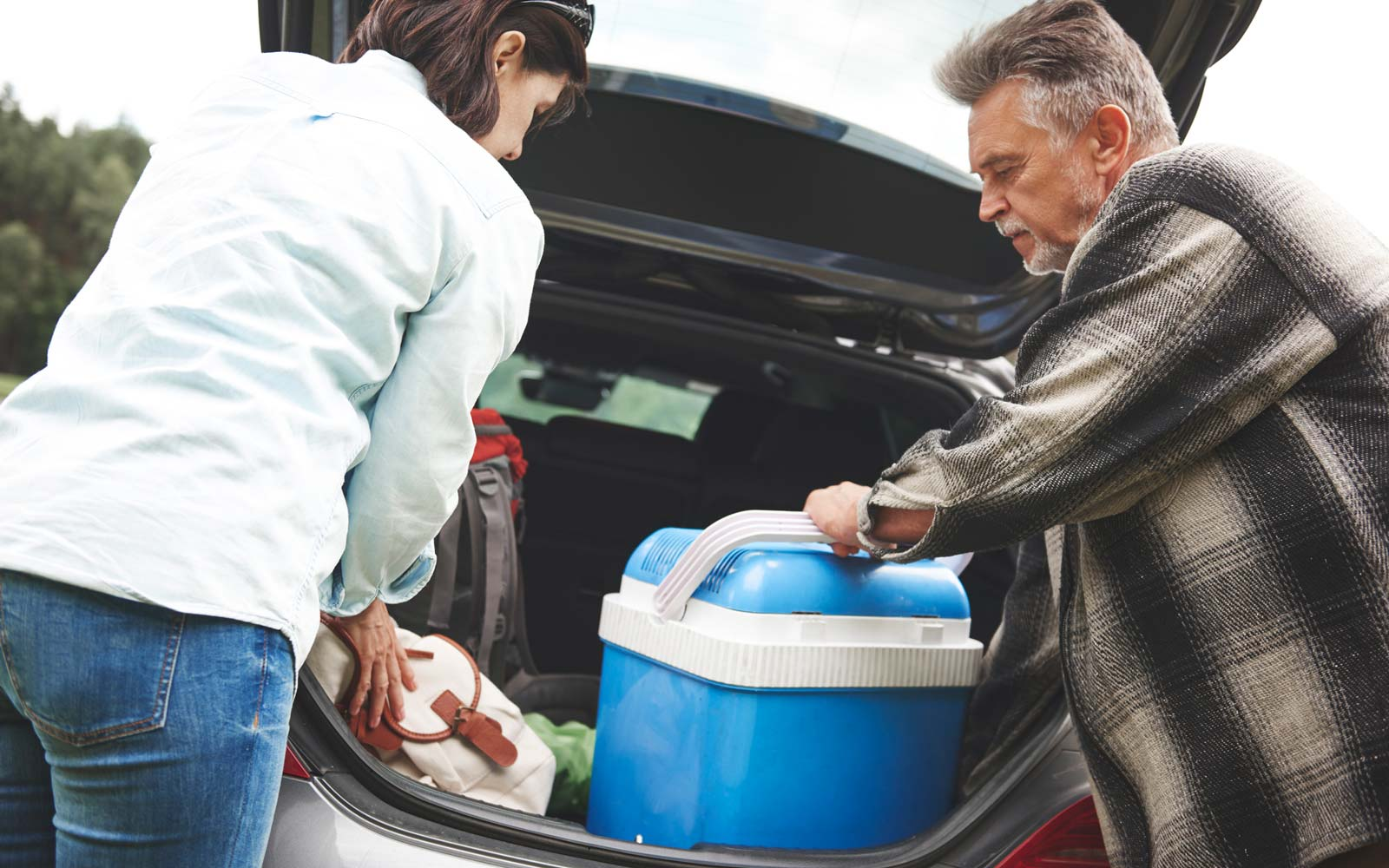 Mature couple removing camping equipment from car boot