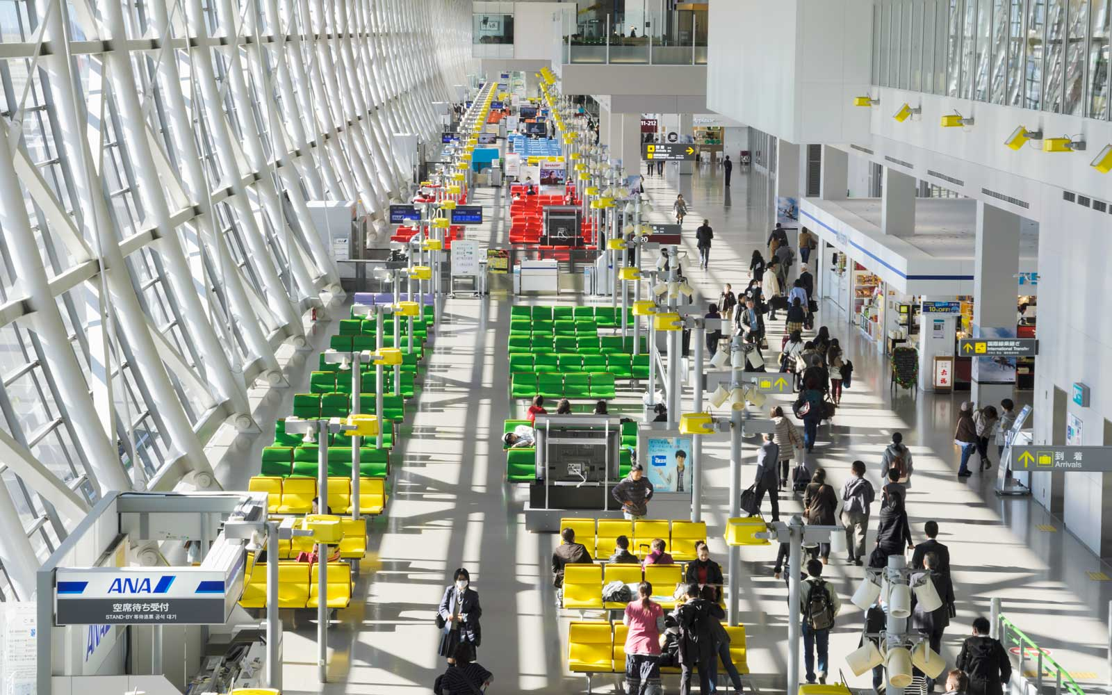 Patterns of brightly coloured seats in the busy departures area of Kansai Airport, near Osaka, Japan
