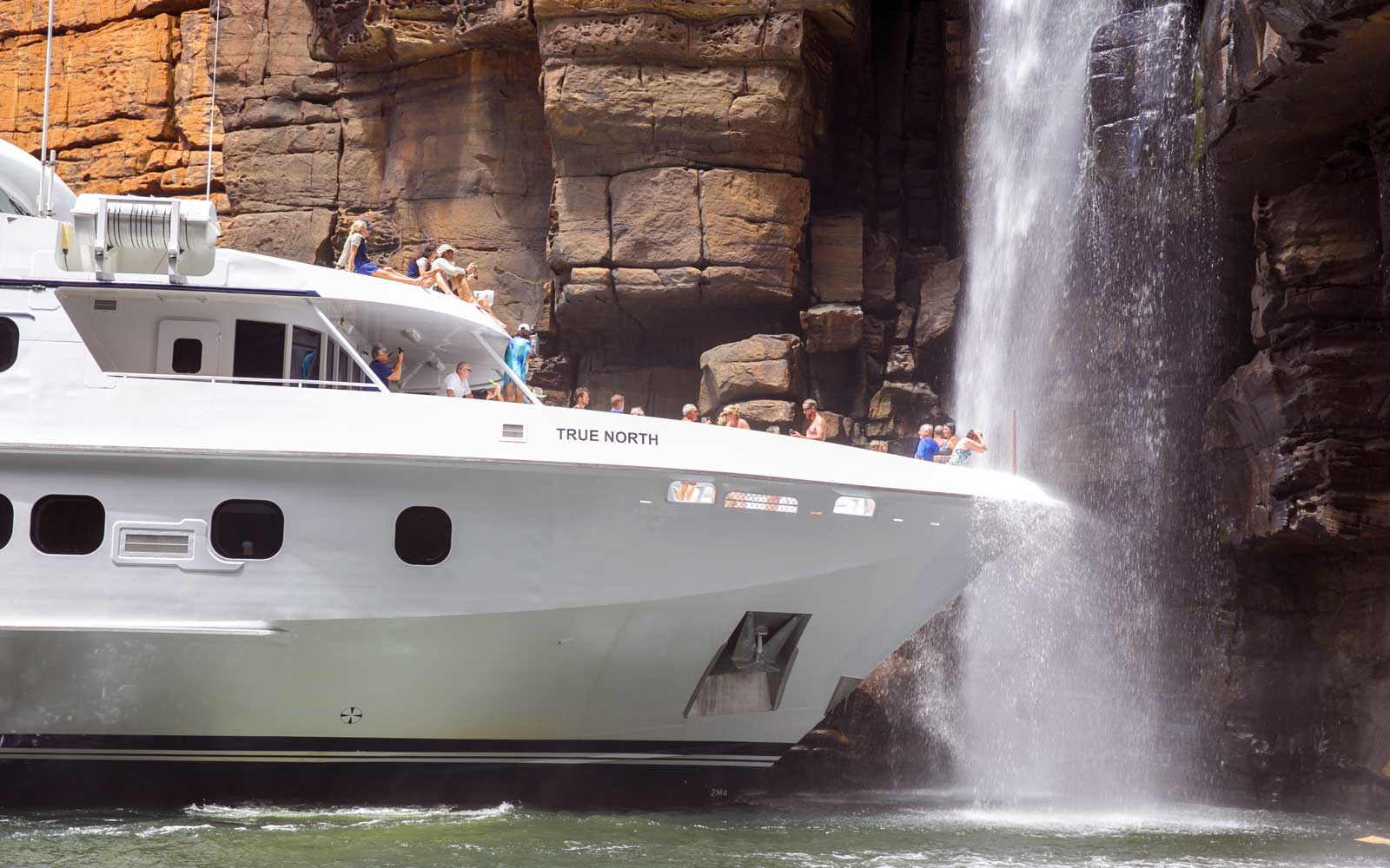 True North boat at waterfall in the Kimberley, Australia